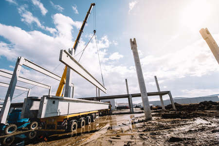 Industrial construction site of prefabricated hall with cement pillars and concrete beams with moving crane working