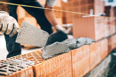 Close up of construction worker details, protective gear and trowel with mortar building brick walls