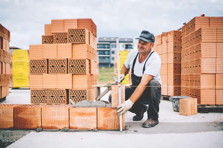 Industrial worker using leveler and tools for building exterior walls with bricks and mortar