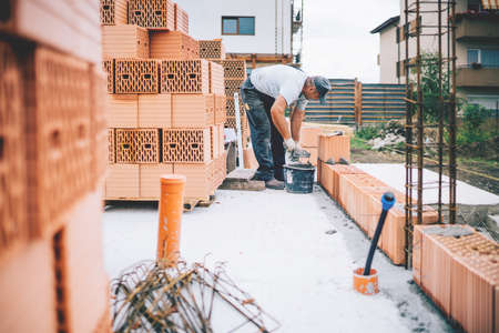 Construction site details - Industrial worker building brick walls