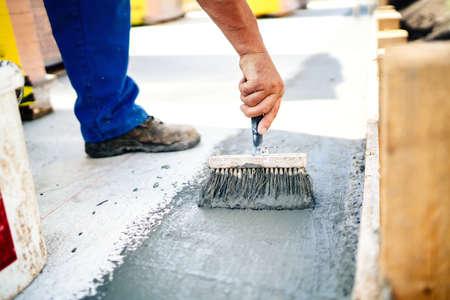 Bauarbeiter mit Bürste und Grundierung für die Hydroisolierung und Abdichtung Haus