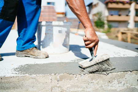 Man using industrial brush for hydro-insulation of concrete foundation 写真素材