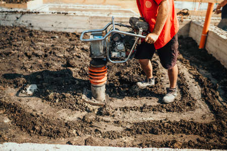 Construction industrial worker compacting soil in house foundation using compactor