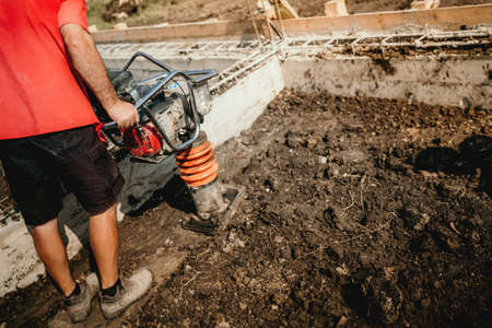 builder worker compacting soil with vibration compaction machine during foundation works