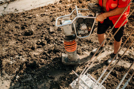Details of construction worker using compactor for earth and soil compacting Banque d'images