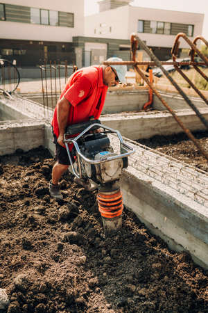 Portrait of construction worker compacting soil with vibration compaction machinery