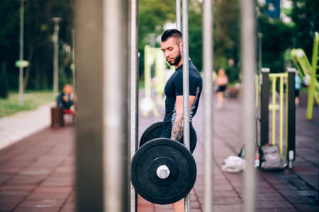 Muscular man training in park. Heavy weight lifting in park with dumbells Foto de archivo