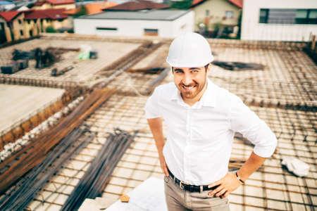 confident, smiling engineer and architect on construction site. Building construction site background Foto de archivo