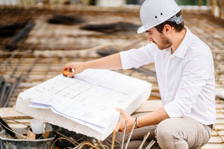 brick walls, infrastructure on construction site. construction engineer reading plans, working on building construction site. 版權商用圖片