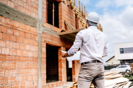 brick walls, infrastructure on construction site. construction engineer reading plans, working on building construction site. Foto de archivo
