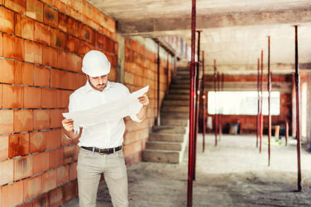 Construction Industry engineer working on site, man reading paper plans and supervising construction works Foto de archivo