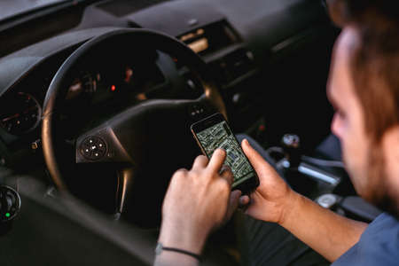 Man using mobile phone for gps tracking in car trip, close up of man using everyday technology