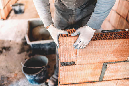 Industrial male worker using trowel and tools for building interior walls with bricks and mortar