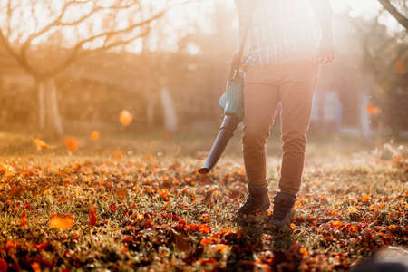 close up details, portrait of gardener using leaf blower and vacuum. Autumn clean up Stockfoto