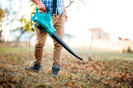 Gardener clearing up leaves using an electric leaf blower tool. Gardening details