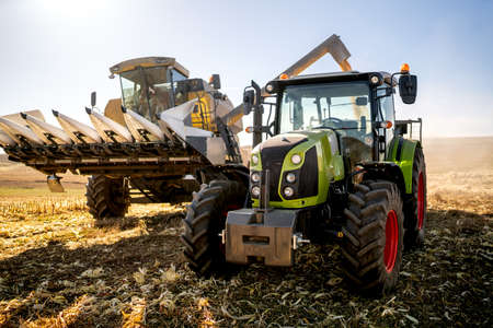 Agriculture industry machinery. Combine harvester and tractor with trailer unloading harvest