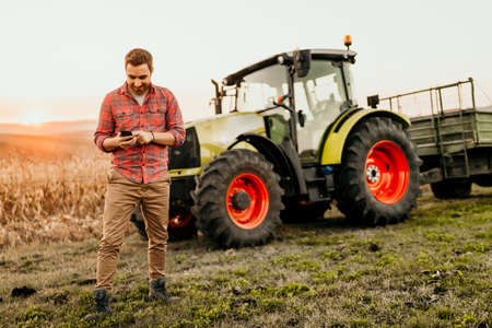Male farmer working on field using smartphone in modern agriculture - tractor background 免版税图像