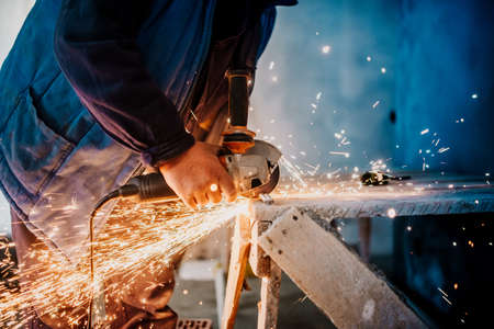 Metalworker cutting iron and metal with a rotary angle grinder and working, generating metal sparks