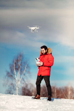 Aerial photography and drone footage details with attractive caucasian man operating drone, flying over blue sky Stock Photo