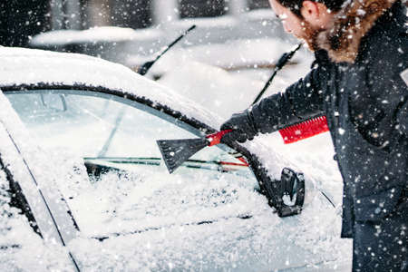 Winter snowfall - people cleaning vehicles. Winter car care with broom, brush and scraper