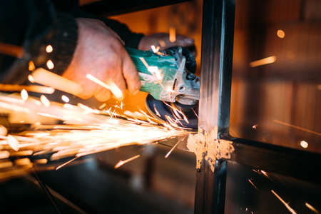 Caucasian male working in construction industry and cutting metal with disc angle grinder