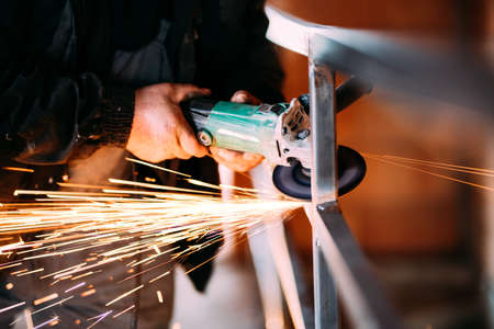 Heavy industry worker cutting steel with angle grinder on construction site