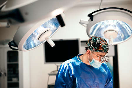 Surgeon doctor performing operation using special lamp lighting, wearing blue surgical mask
