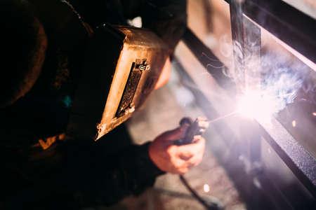 Professional worker, technician welding with equipment protective mask welder