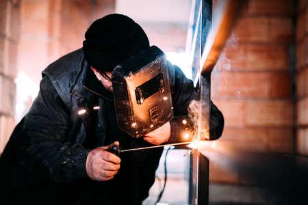 Portrait of industrial Worker laborer at construction site welding steel structure