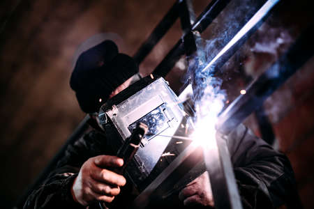 portrait of professional welder with protection gear working on metal railings