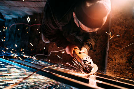 industrial worker using angle grinder on construction site and throwing sparks. Metal railings production