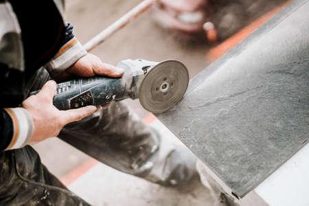 Dettagli del sito in costruzione - strumento industriale, lavoratore con smerigliatrice angolare che taglia pietra di marmo