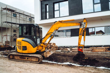 Mini heavy duty excavator moving earth for foundation building. Industrial machinery on construction site, 免版税图像