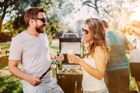 Freunde, die eine Grillparty mit Getränken, Essen und Kochen im Freien in der Natur veranstalten Standard-Bild