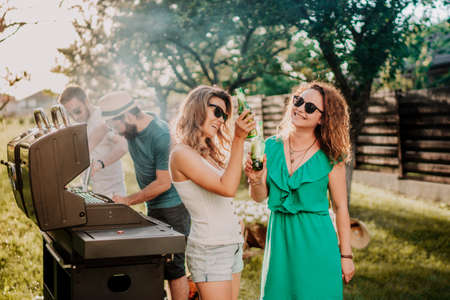 Friends having a barbecue party, girls laughing and smiling, drinking and cooking