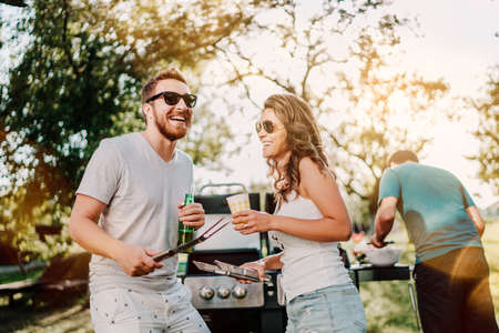 Grupo de amigos sonrientes en vacaciones tomando cervezas y cocinando en una barbacoa en el jardín. Estilo de vida, concepto de ocio