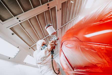 Detalles de la industria automotriz: ingeniero mecánico con pistola rociadora y pintando un automóvil rojo Foto de archivo