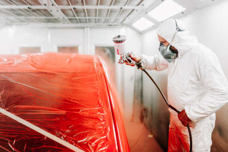 automotive industry engineer using spray gun and painting a red car