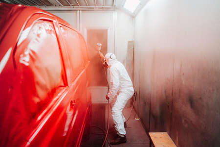 automotive industry manufacturing - mechanic engineer using spray gun and painting a red car Фото со стока