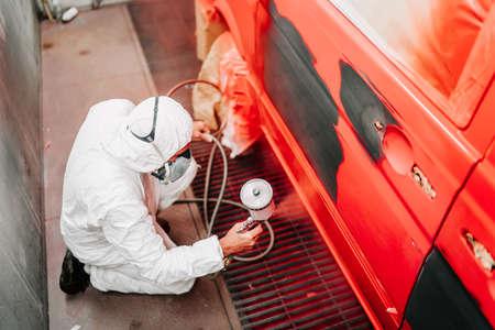 Pittore del meccanico che dipinge un'automobile rossa, un furgone in cabina speciale dettagli dell'industria automobilistica Archivio Fotografico