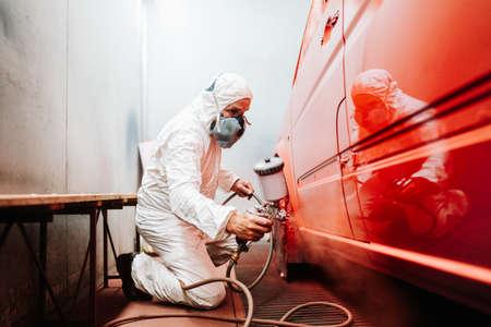 Mechaniker männlicher Arbeiter, der ein Auto in einem speziellen Malkasten bemalt und ein weißes Kostüm und Schutzausrüstung trägt Standard-Bild