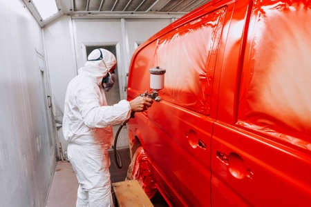 Auto mechanic working and painting a red van in a special booth