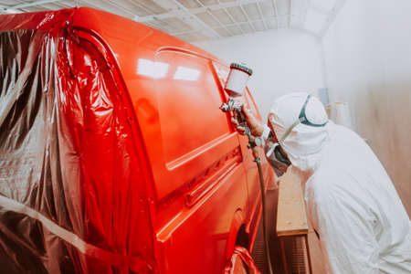 Automotive industry - engineer painting and working on a red bodywork of a car and wearing protective gear