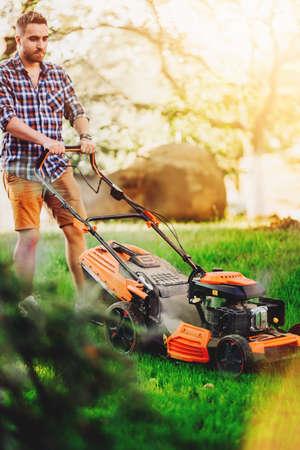 Portrait of handsome gardenere worker using lawnmower and cutting the garden grass