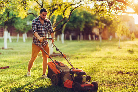 lawncare and landscaping concept - garden maintainance with gardener working and cutting grass