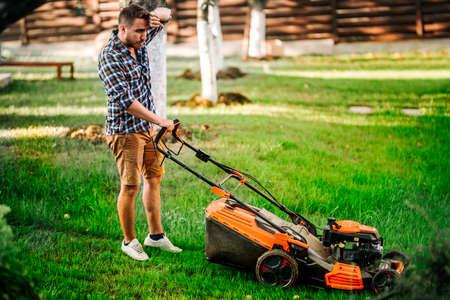 Portrait of hard working gardener using lawnmower and cutting grass Imagens