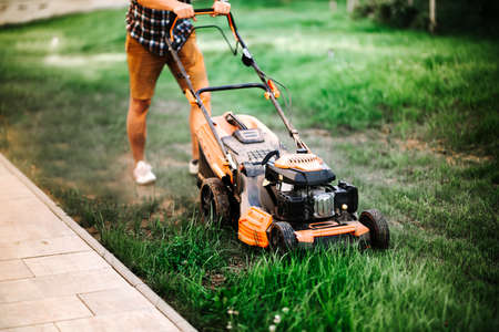 Gardening and landscaping concept - worker, gardener working with lawnmower and cutting grass in garden