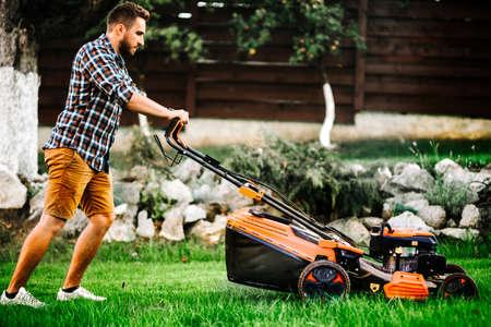 Details and portrait of gardener using industrial manual lawnmower