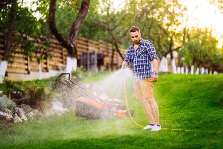 Smiling gardener watering backyard lawn 写真素材