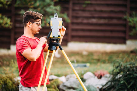 Portrait of surveyor engineer using equipment with theodolite and total station